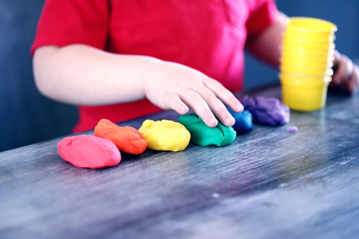 enfant en train de jouer à la pâte à modeler activités nounou