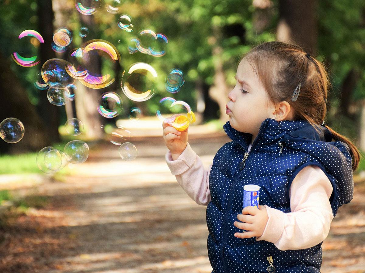 petite fille qui fait des bulles de savon garde à domicile babysitting