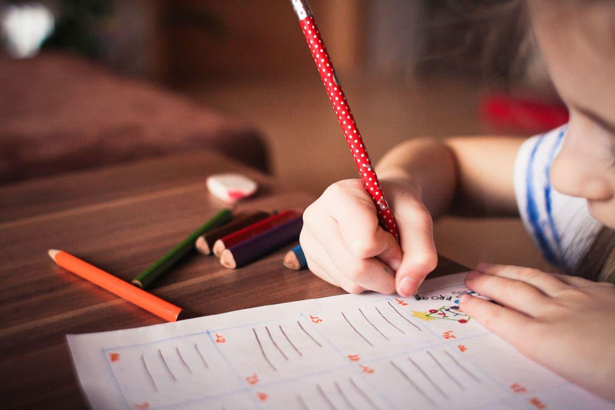 petite fille en train de faire ses devoirs garde d'enfant à domicile sortie d'école